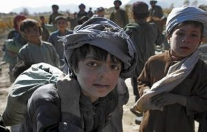 An Afghan boy poses for a photographer as a military convoy form First Battalion, 502nd Infantry Regiment, 101st Airborne Division, stops in Panjwai district, Afghanistan's Kandahar province, Tuesday, Nov. 30, 2010.(AP Photo/Alexander Zemlianichenko)